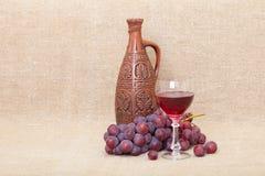 Composición del arte de la botella, de las uvas y del vidrio de la arcilla Fotografía de archivo libre de regalías