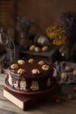 Composición oscura del misterio de la comida de la torta de chocolate con el libro y las nueces Imagen de archivo
