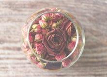 Composición romántica con las rosas en un florero con el fondo de madera Fotos de archivo libres de regalías
