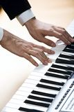 Composing. Isolated on pink human hands playing the piano Stock Photography