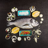 Composing with dorado raw fish, lemon and spices on black textured background. Top view Stock Photo