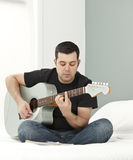 Composing at home. Man composing music using electric-acoustic guitar stock image