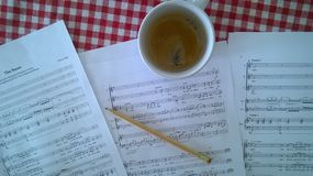 Composing. Some music sheets, a cup of coffee and a pencil Stock Image