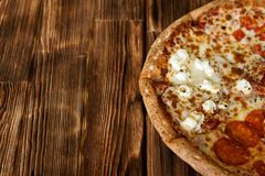 Composite-assorted pizza on a natural wooden surface of pine boards. Daylight. Close-up. Free space to sign royalty free stock image