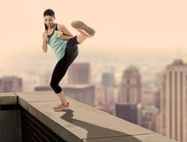 Composite of attractive furious sport woman in fight and martial arts kick workout on urban rooftop edge with a skyline city Royalty Free Stock Photography