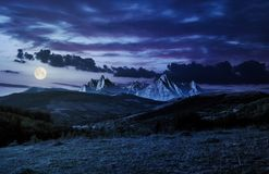 Composite of countryside at night. In full moon light. gorgeous cloudscape over the mountains with rocky peaks royalty free stock photo
