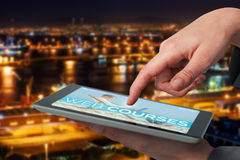 Composite 3d image of businesswoman hand using digital tablet. Businesswoman hand using digital 3D tablet against illuminated harbor against cityscape Royalty Free Stock Image
