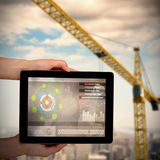 Composite 3d image of close-up of hands holding digital tablet. Close-up of hands holding digital tablet against 3d image of yellow crane Stock Images