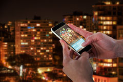 Composite 3d image of close-up of man holding smart phone. Close-up of man holding 3D smart phone against illuminated towers in city Royalty Free Stock Photography