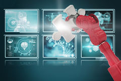 Composite 3d image of cropped of red robotic hand holding puzzle piece. Cropped of 3D red robotic hand holding puzzle piece against screens with blue interface Stock Photography
