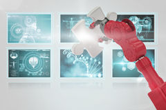 Composite 3d image of cropped of red robotic hand holding puzzle piece. Cropped of 3D red robotic hand holding puzzle piece against screens with blue interface Royalty Free Stock Photos