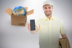 Composite 3d image of handsome delivery man showing mobile phone. Handsome delivery man showing 3D mobile phone against grey background Stock Image