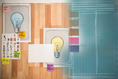 Composite 3d image of light bulb charts attached on wooden wall. 3D image of light bulb charts attached on wooden wall against illuminated blue grid Stock Image