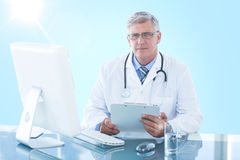 Composite 3d image of portrait of confident male doctor sitting at computer desk. Portrait of confident male doctor sitting at 3D computer desk against blue Royalty Free Stock Image