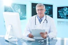 Composite 3d image of portrait of confident male doctor sitting at computer desk. Portrait of confident male doctor sitting at computer desk against 3D blue Stock Photo