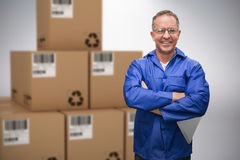 Composite 3d image of smiling warehouse manager standing with arms crossed Stock Photography