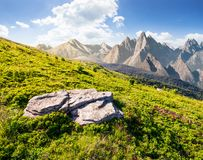 Composite of grassy meadow and rocky mountains. Beautiful unrealistic landscape in summertime royalty free stock images