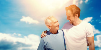 Composite image of adult son hugging his old father. Adult son hugging his old father against cloudy sky with sunshine stock photo
