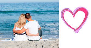 Composite image of affectionate couple sitting on the sand at the beach Royalty Free Stock Photo