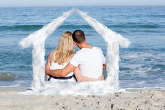 Composite image of affectionate couple sitting on the sand at the beach Royalty Free Stock Image
