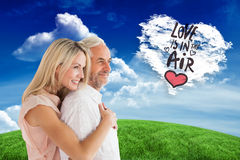 Composite image of affectionate couple standing and hugging Royalty Free Stock Image