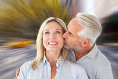 Composite image of affectionate man kissing his wife on the cheek Royalty Free Stock Photos