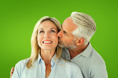 Composite image of affectionate man kissing his wife on the cheek Royalty Free Stock Photography