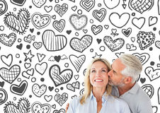 Composite image of affectionate man kissing his wife on the cheek Stock Photos