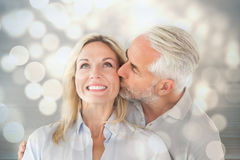 Composite image of affectionate man kissing his wife on the cheek Stock Photo