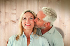 Composite image of affectionate man kissing his wife on the cheek Royalty Free Stock Image