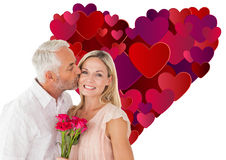Composite image of affectionate man kissing his wife on the cheek with roses Royalty Free Stock Images