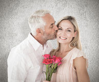 Composite image of affectionate man kissing his wife on the cheek with roses Royalty Free Stock Photography