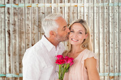 Composite image of affectionate man kissing his wife on the cheek with roses Stock Photo