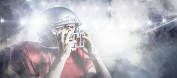 Composite image of aggressive american football player holding helmet. 3D Aggressive American football player holding helmet against splashing of powder Royalty Free Stock Photography
