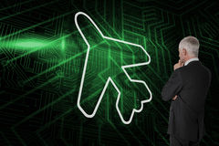 Composite image of airplane and businessman watching Stock Image