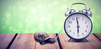 Composite image of alarm clock. Alarm clock against green abstract light spot design Stock Photography