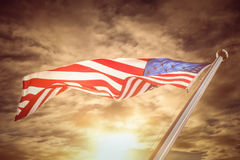 Composite image of american flag. American flag against cloudy sky Stock Image