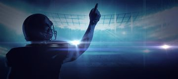 Composite image of american football player in helmet pointing upwards royalty free stock photography