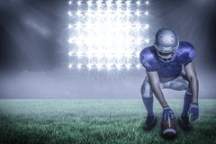 Composite image of american football player holding ball while crouching with 3d Royalty Free Stock Photo