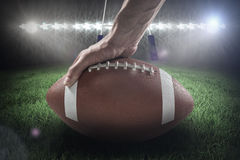 Composite image of american football player holding ball 3D. American football player holding ball against rugby pitch 3D Royalty Free Stock Photography
