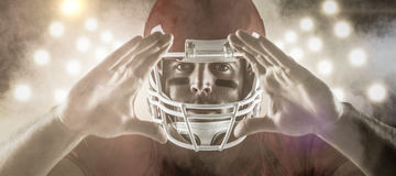 Composite image of american football player making hand gesture. 3D American football player making hand gesture against splashing of color powder Royalty Free Stock Images