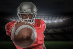 Composite image of american football player in red jersey holding ball. 3D American football player in red jersey holding ball against rugby stadium Royalty Free Stock Image