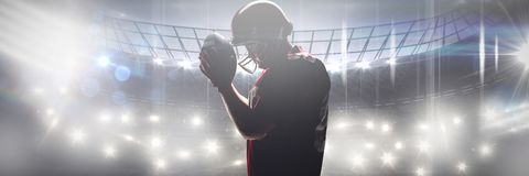 Composite image of american football player standing with rugby helmet and ball. American football player standing with rugby helmet and ball against american royalty free stock images
