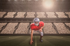 Composite image of american football player taking position while playing with 3d. American football player taking position while playing against football Royalty Free Stock Photography