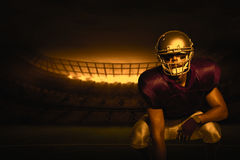 Composite image of american football player in uniform crouching. 3D American football player in uniform crouching against rugby stadium Stock Images