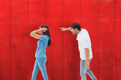 Composite image of angry boyfriend shouting at girlfriend. Angry boyfriend shouting at girlfriend against red wooden planks royalty free stock photography