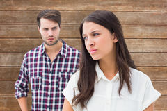 Composite image of angry brunette not listening to her boyfriend Royalty Free Stock Photo