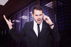 Composite image of angry businessman gesturing on the phone Stock Photos
