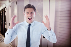 Composite image of angry businessman shouting. Angry businessman shouting against data center Stock Photos