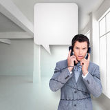 Composite image of angry businessman tangle up in phone wires Royalty Free Stock Photos